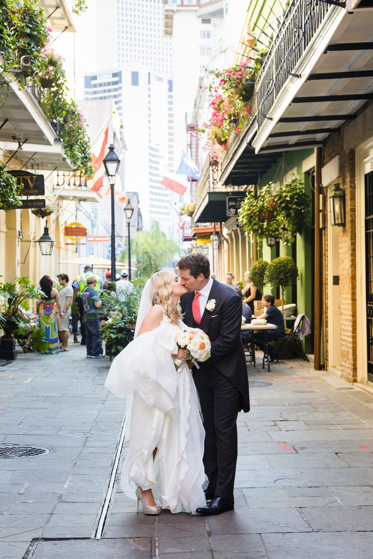 bride and groom kissin in the french quarter streets surrounded by buildings