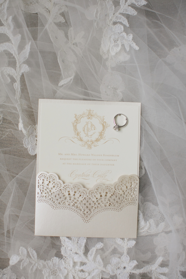Ivory wedding invitation with a gold crest, white lace overlay