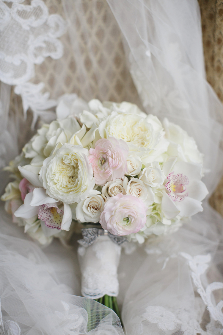 Gorgeous wedding bouquet with white and pink ranunculus and white roses sitting on a chair with the white lace veil behind it