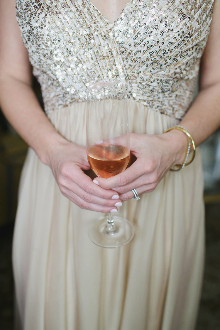 Gold and champagne colored dress and a glass of rose