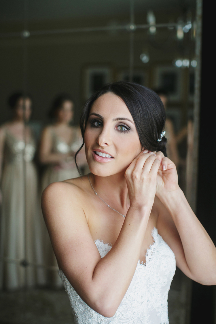 Bride in a strapless white lace wedding dress putting on her earrings with her bridesmaids in the back