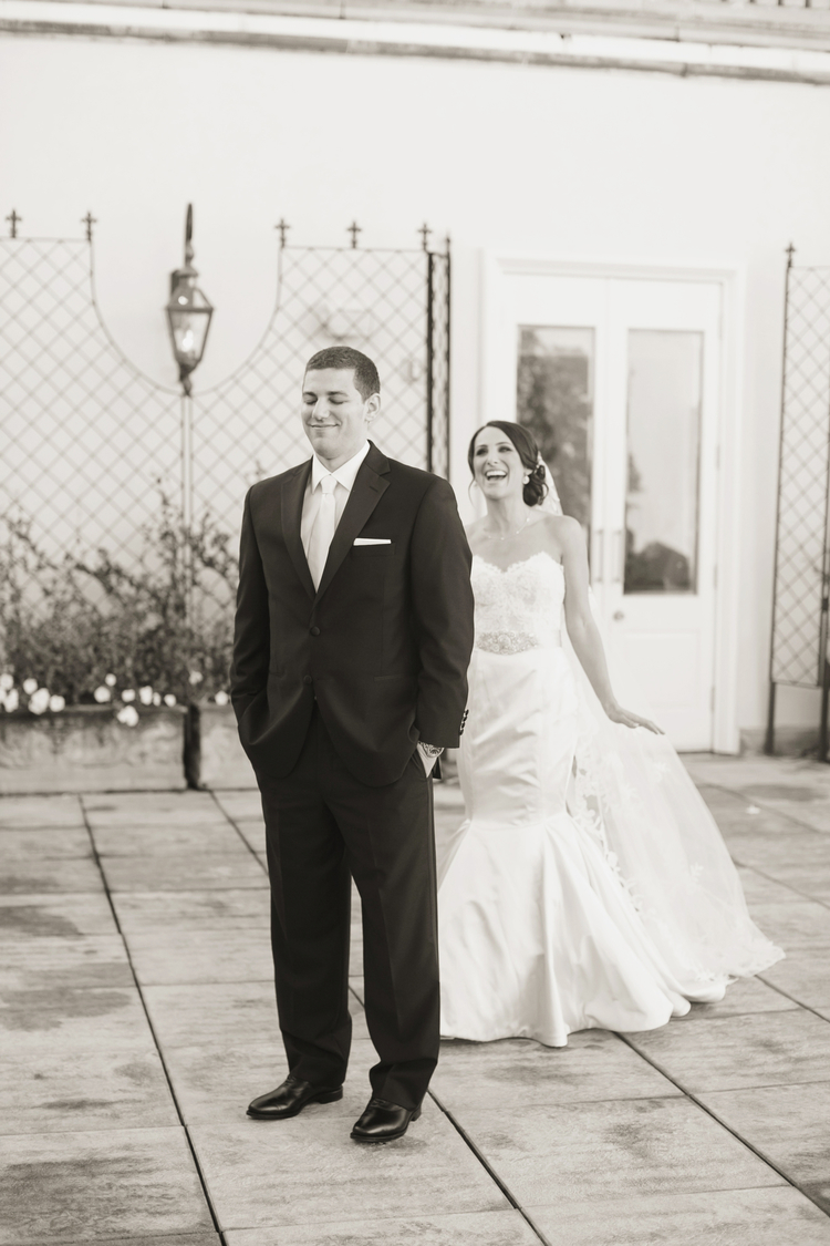 """Bride walking behind her groom to do a """"first look"""" in a courtyard"""