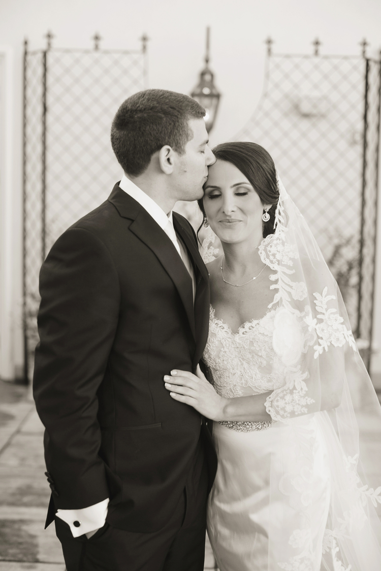 Groom kissing his bride on the forehead with her lace veil over her shoulder