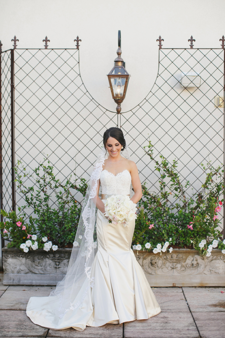 Gorgeous bride standing in a courtyard with greenery in the background and her lace veil coming over her shoulder