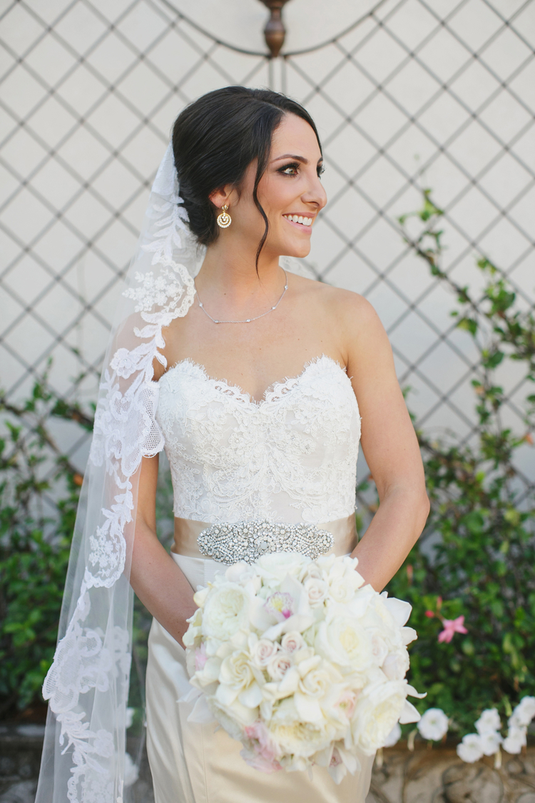 Bride in a strapless lace wedding dress with an ivory sash and a long white lace veil holding her white lush bouquet