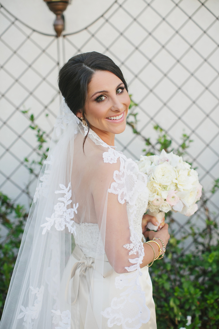 Bride Looking over her shoulder with a long white lace veil and a white floral bouquet