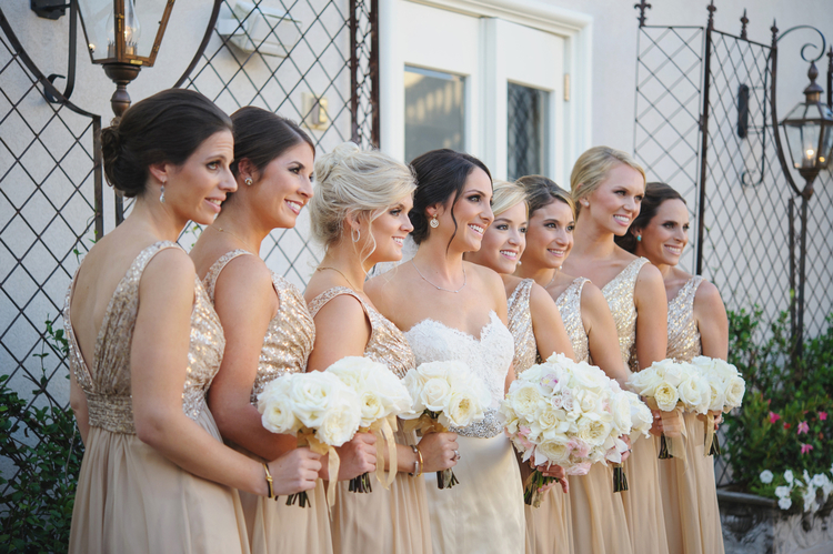 bride with bridesmaids smiling together in a courtyard before the ceremony