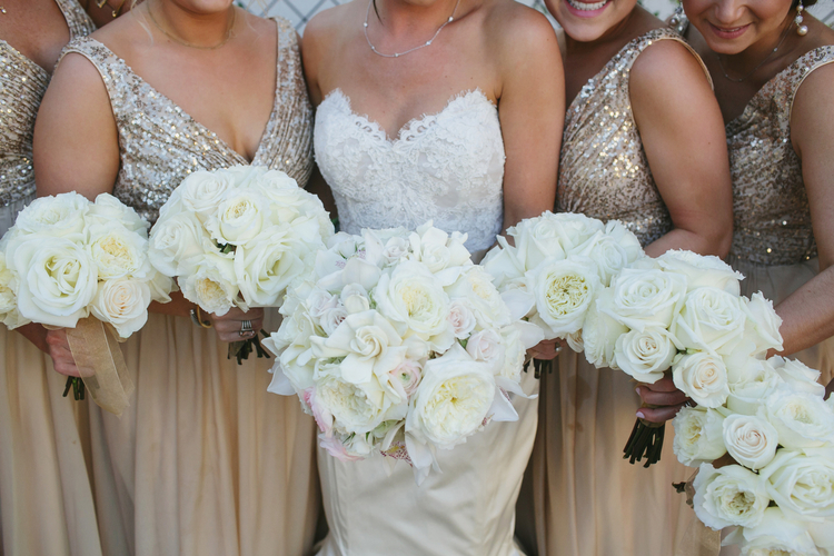 Bride and bridesmaids holding out white rose bouquets in gold dresses