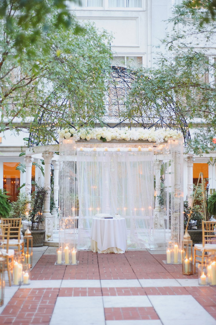 Wedding ceremony set up under an iron arch with white roses and a white backdrop
