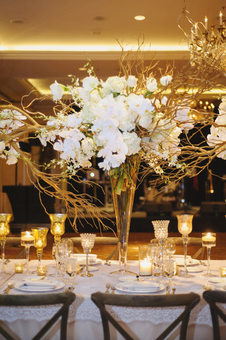 Tall floral table arrangement with white orchids and white roses