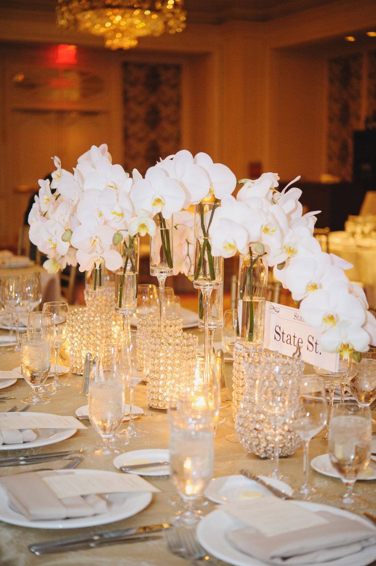 Beautiful white orchids as the centerpiece of a table cascading down the middle