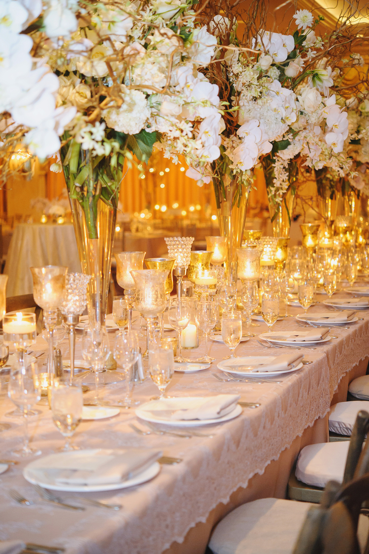 Long table at a wedding reception with tall flower arrangements down the middle and tea lights under them