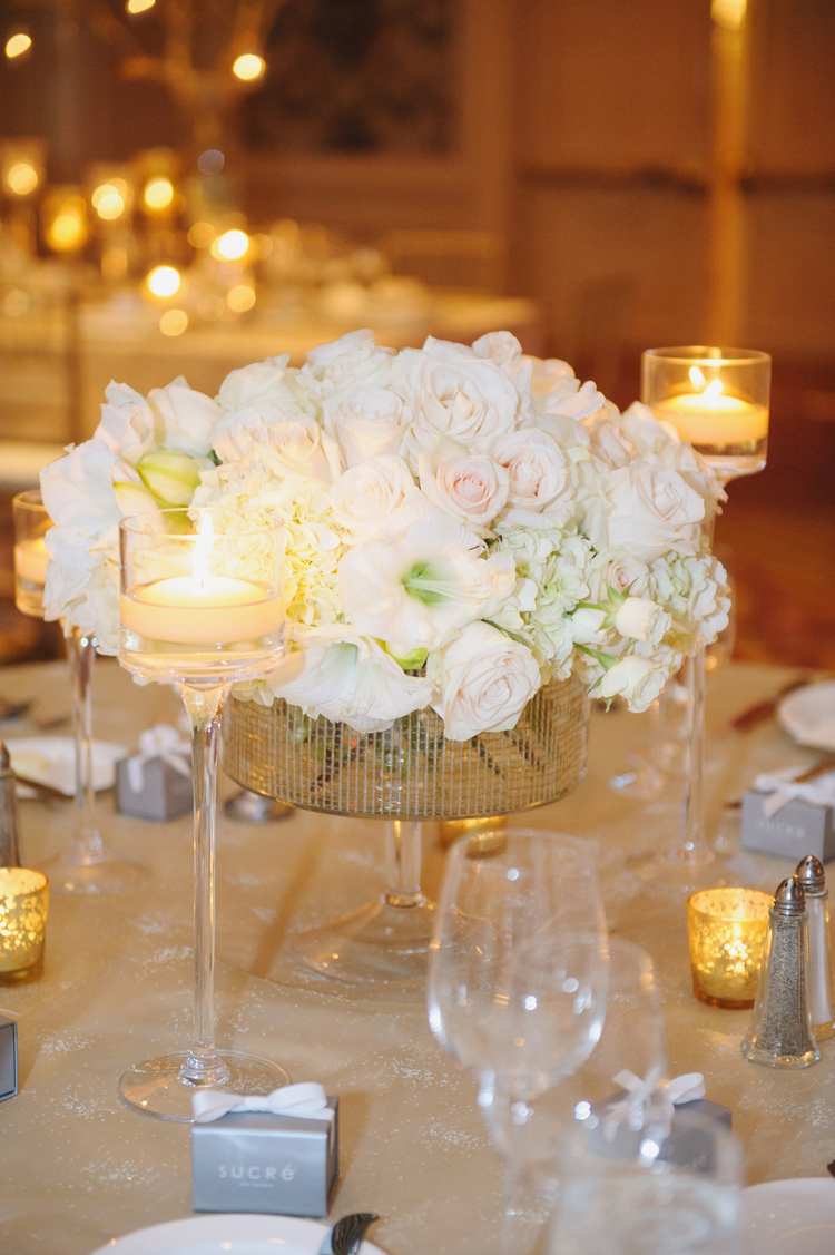 Low floral arrangement on a table with white and light pink roses and two tall candles next to it