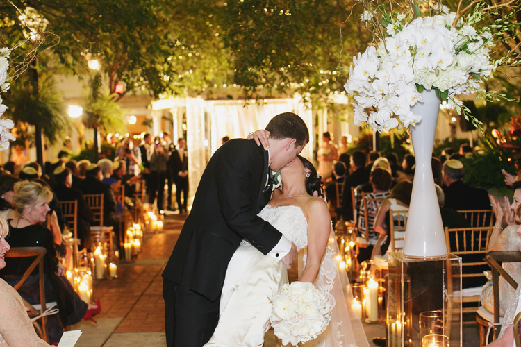 Groom dipping his bride at the end of the aisle of the ceremony with white floral orchid arrangements next to the,