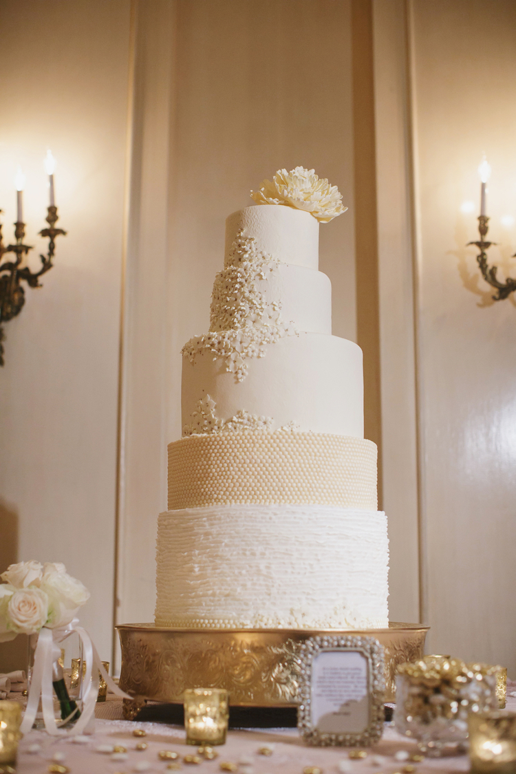 5 tier white wedding cake with detailing and a white flower on the top layer