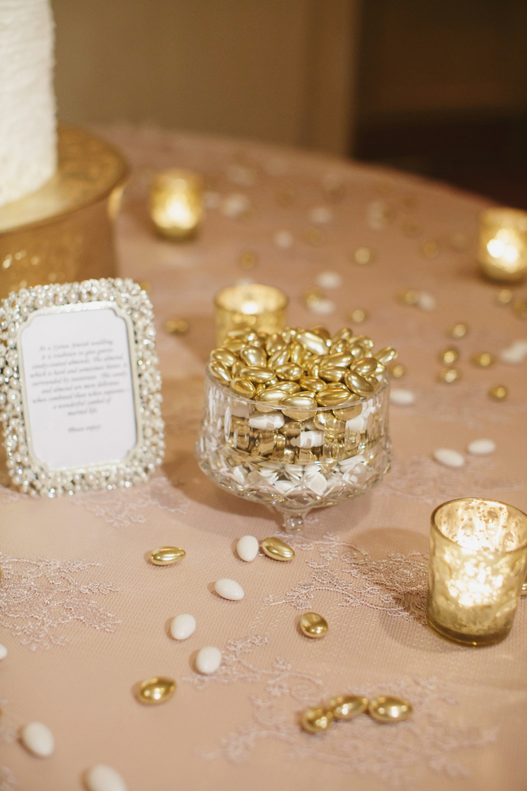 Gold beans sitting in a crystal jar next to the wedding cake