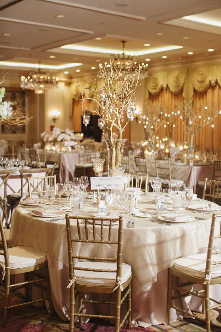 Wedding reception room with round tables and tall tree like centerpieces with tea lights hanging