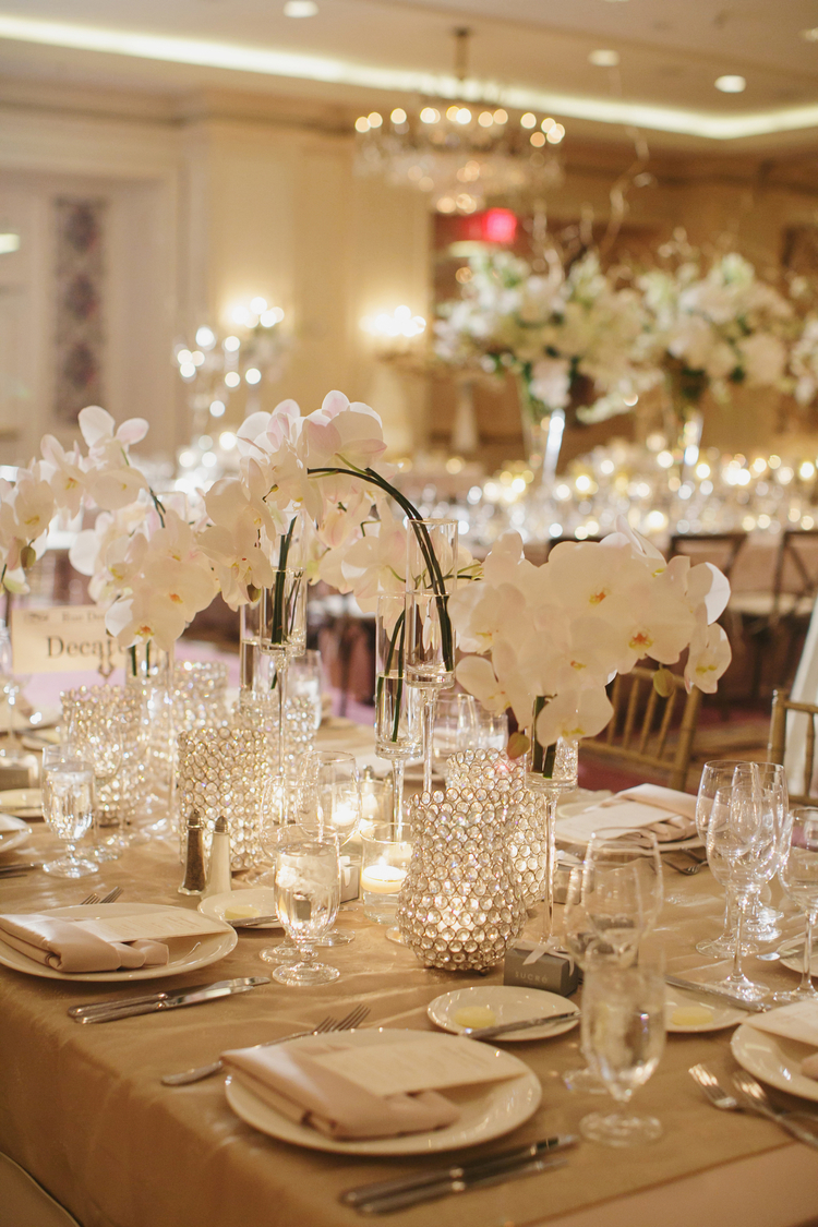 Cascading white orchid arrangements in the center of a table with tea lights around it