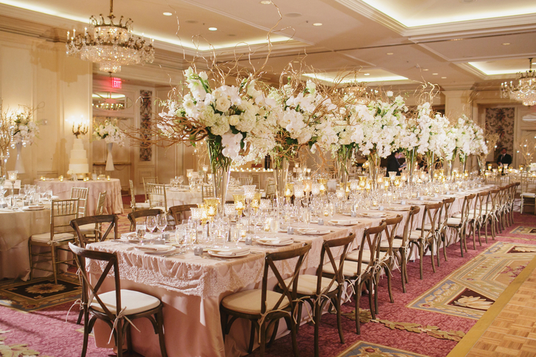 Long table with wood cross back chairs and tall white and green floral arrangements dow the center