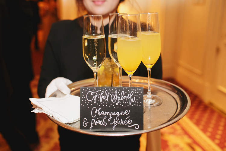 Silver tray with champagne and mimosas held by a server