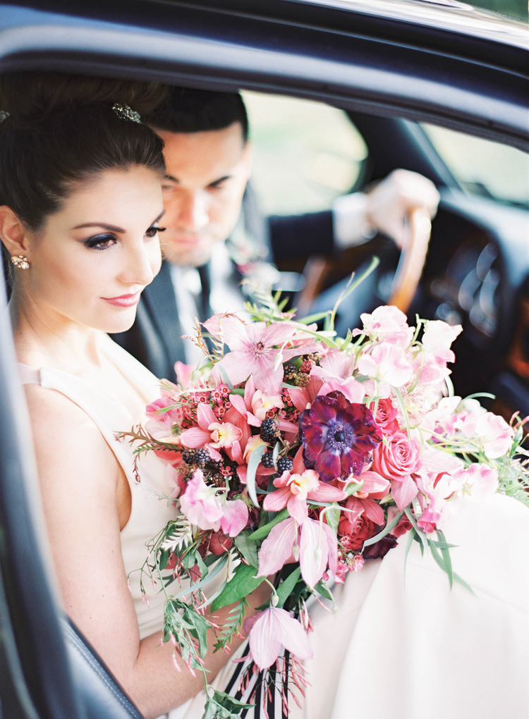 Bride getting out of a car holding a floral bouquet with light and dark pink flowers and some greenery