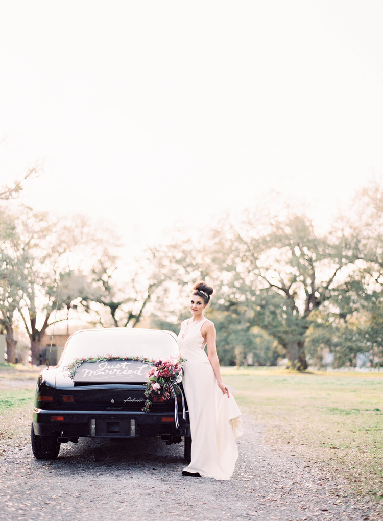Bride standing by a black getaway car with a just married sign and greenery around it