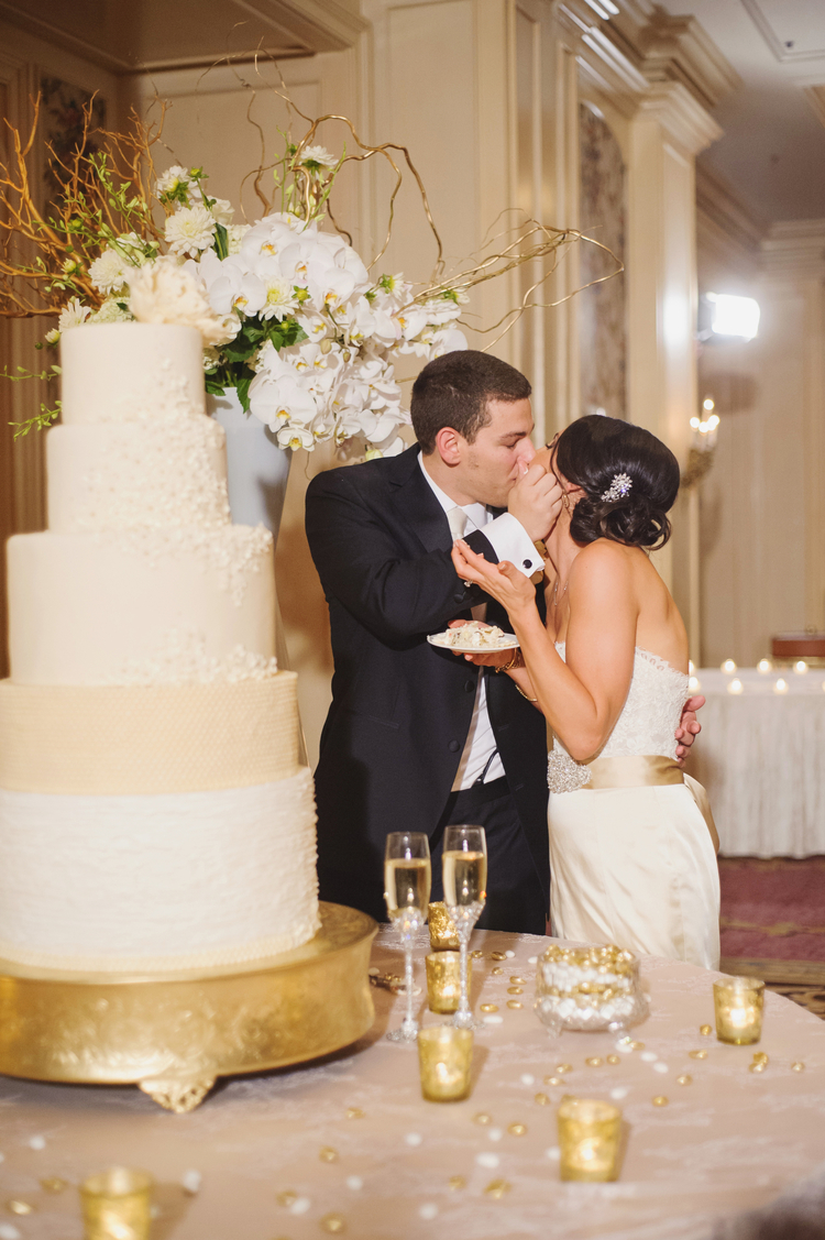 Bride and groom feeding each other cake next to a white orchid arrangement