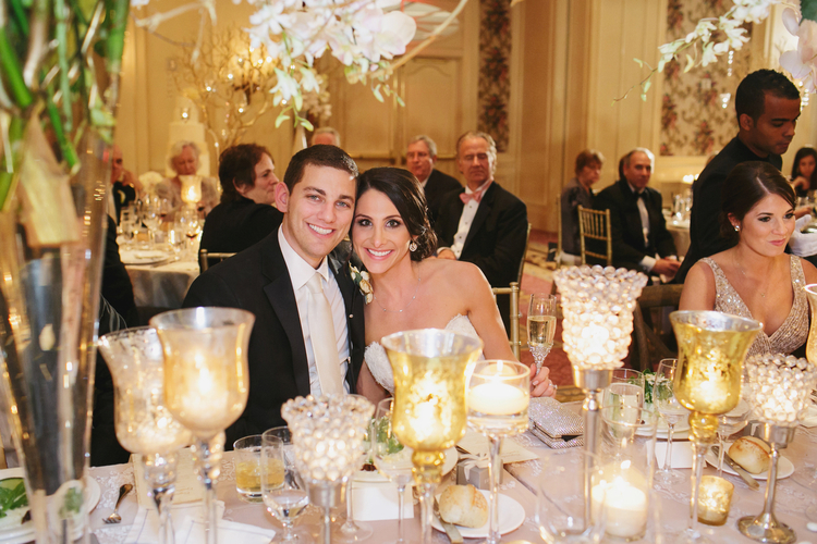 Bride and groom sitting down at their table eating and smiling with guests