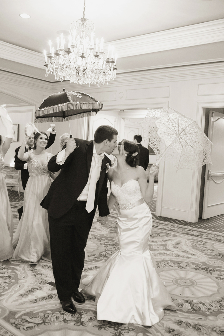 Bride and groom holding up their umbrellas getting ready to second line out of their reception with guests