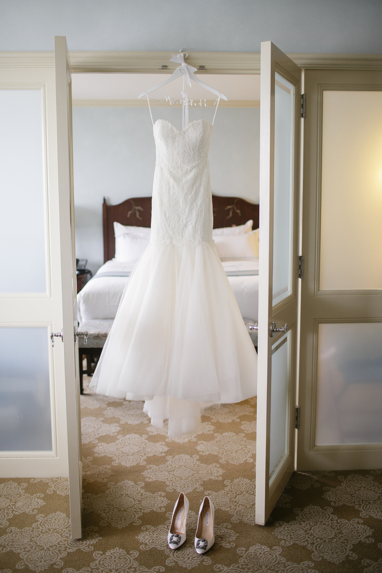 Beautiful white strapless wedding dress hanging from a personalized hanger in a doorway
