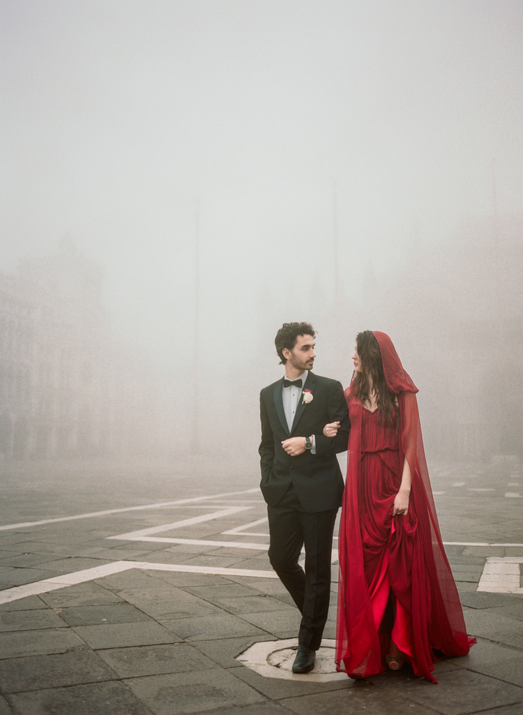 Bride in a  red hooded dress hooked arms with her groom walking through Piazza San Marco