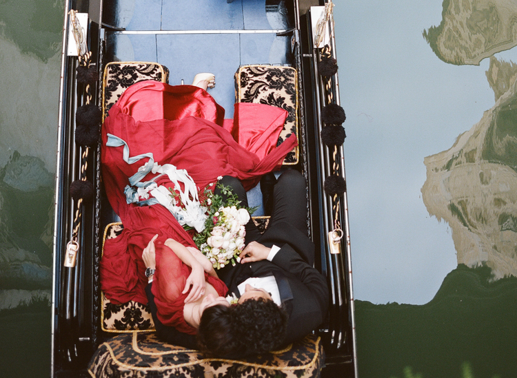 Arial view of bride and groom in a gondola with gold and black detailing