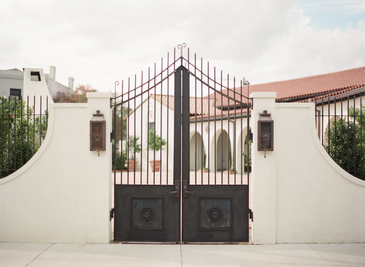 Tall two door iron gate with white stucco siding and bronze lanterns in front of Il Mercato in New Orleans