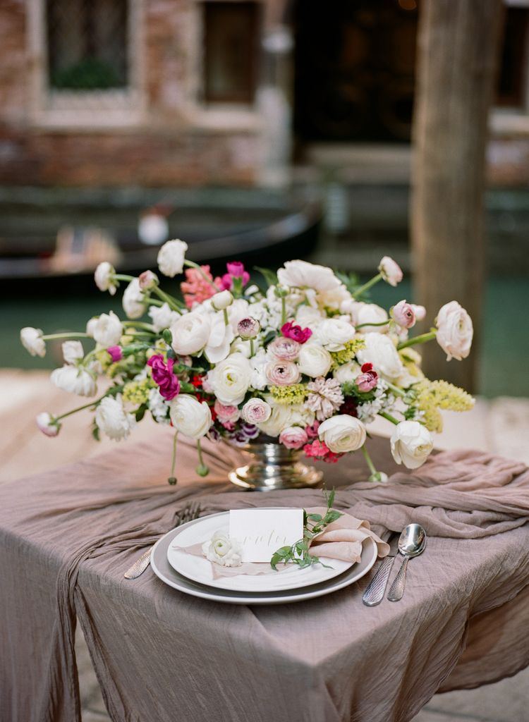 Beautiful lush white, pink and green floral arrangement sitting on a blush color table linen with a name card