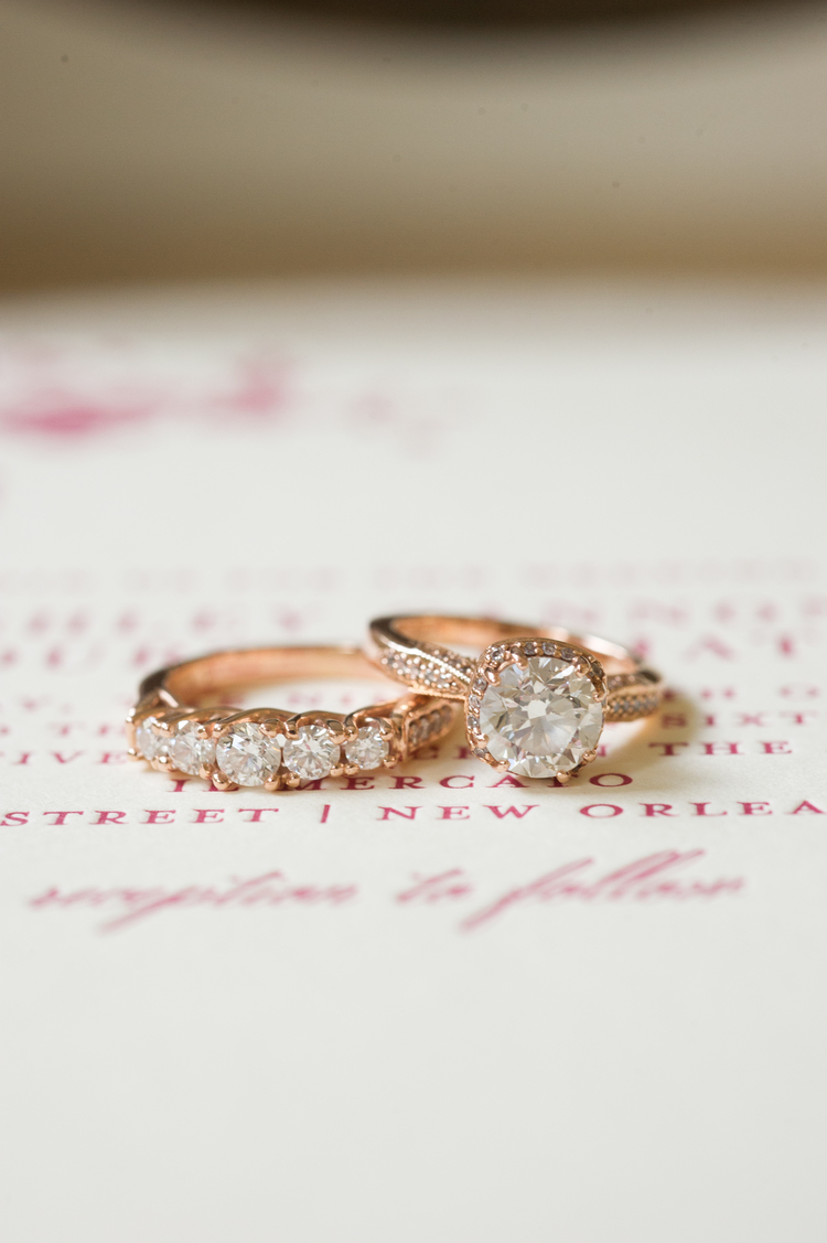 Rose gold engagement and wedding ring sitting on the invitation with pink writing
