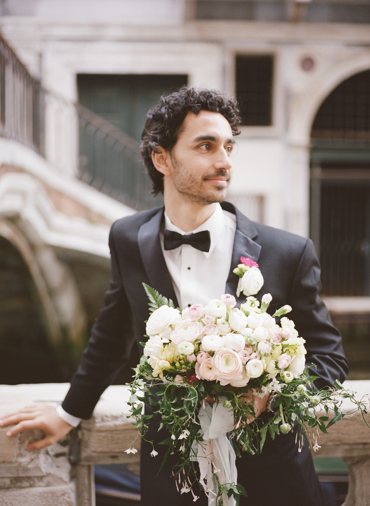 Groom wearing a tux holding his brides bouquet with white, blush and greenery