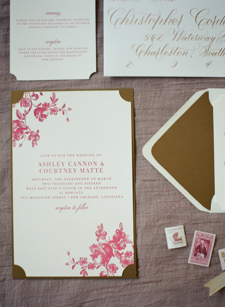 Wedding invitation on white paper with pink lettering and gold detailing