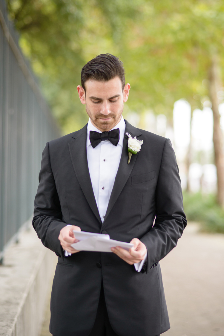 Groom in a black tux reading a letter from the bride