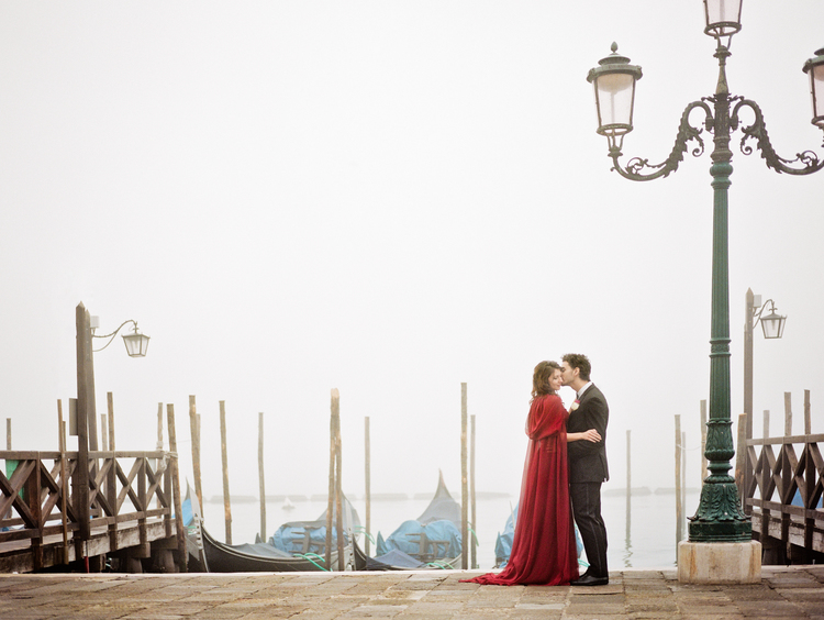Bride and groom kissing in front of gondolas in Venice, Italy