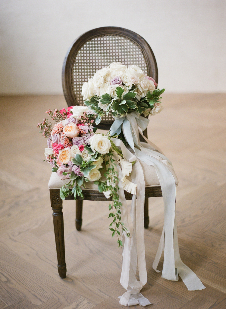 Wedding bouquets with white, pink and purple flowers and light blue sashes sitting on a round back chair