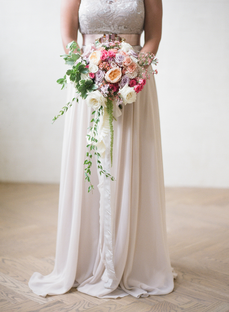 Bride holding her lush bouquet with pink, peach, white, and purple flowers with greenery hanging
