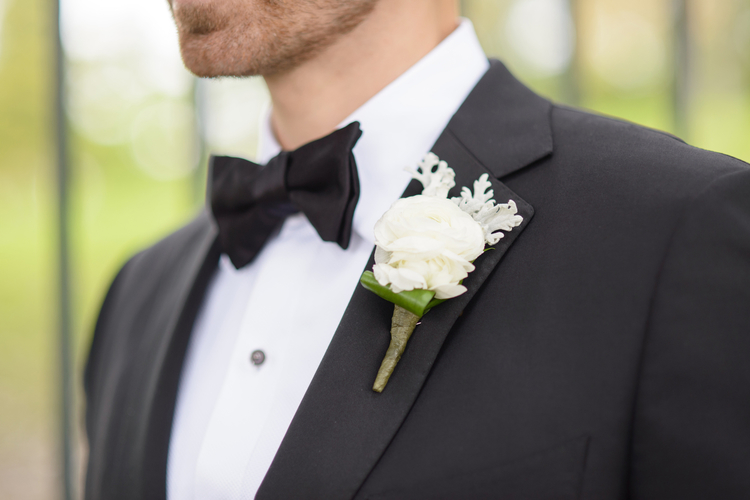 Grooms black and white tux with a white rose boutonniere