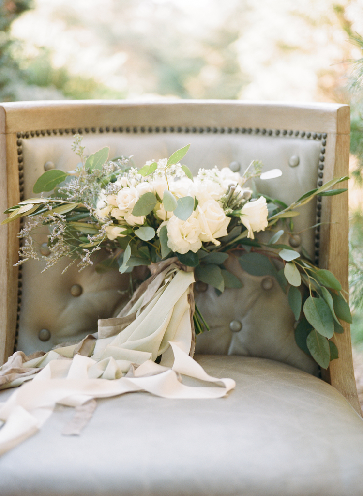 White floral bouquet with eucalyptus and an ivory sash sitting on a taupe chair