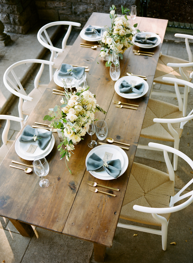 Wooden table set with white plates, gold flatware, blue napkins and white rose floral centerpieces in the middle