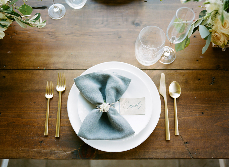 Table setting with white plates, light blue napkins, gold flatware sitting on a mahogany table