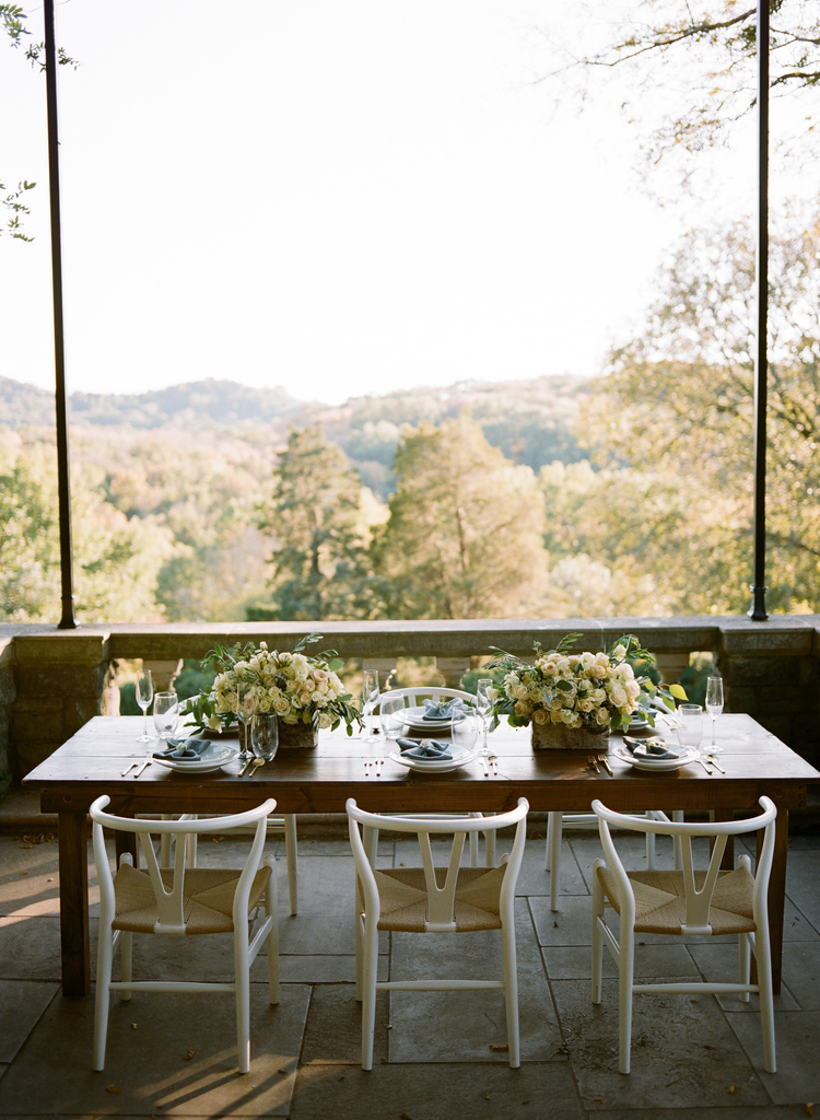 Wooden table, white chairs, white rose floral centerpieces with a lush forrest in the background