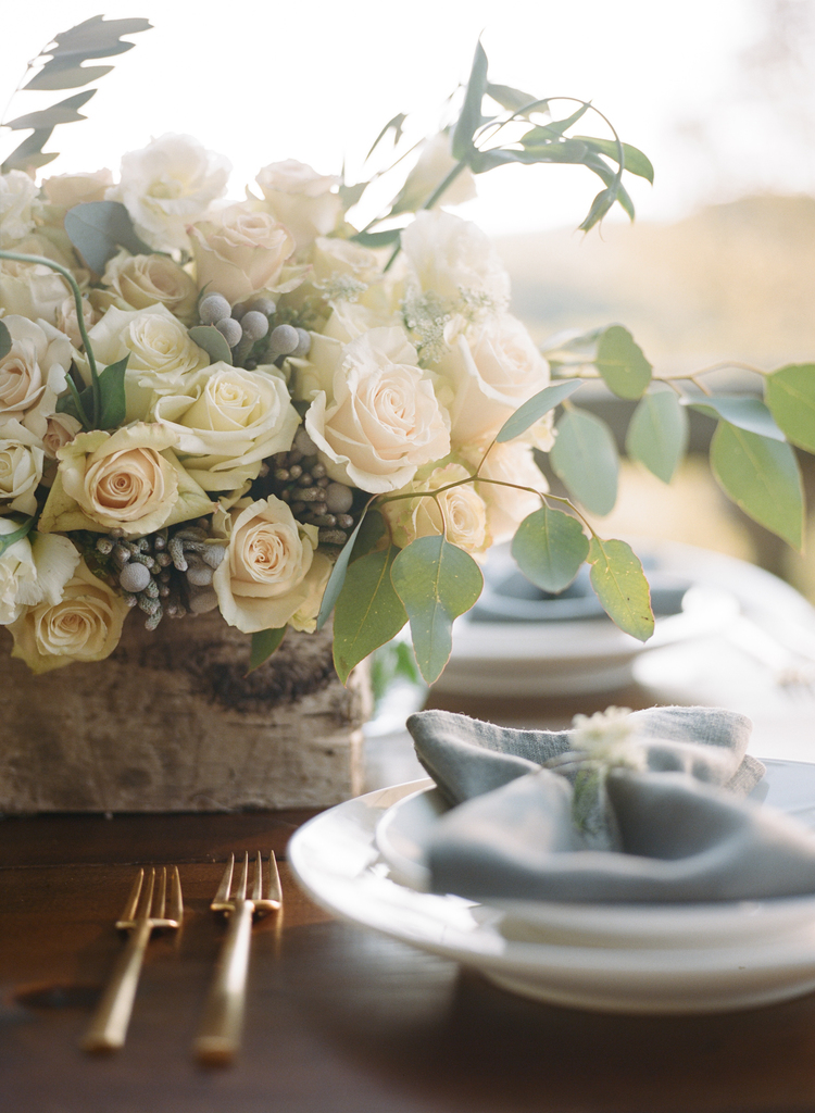 White roses in a table arrangement with eucalyptus next to light blue napkins