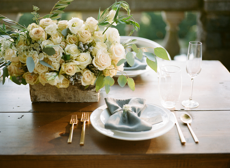 Table setting with white plates, gold flatware, and a white rose centerpiece