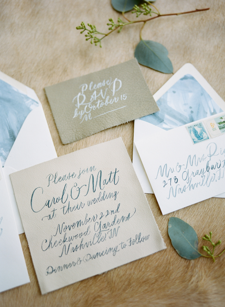 Beige wedding invitation with blue calligraphy wording and olive green RSVP cards