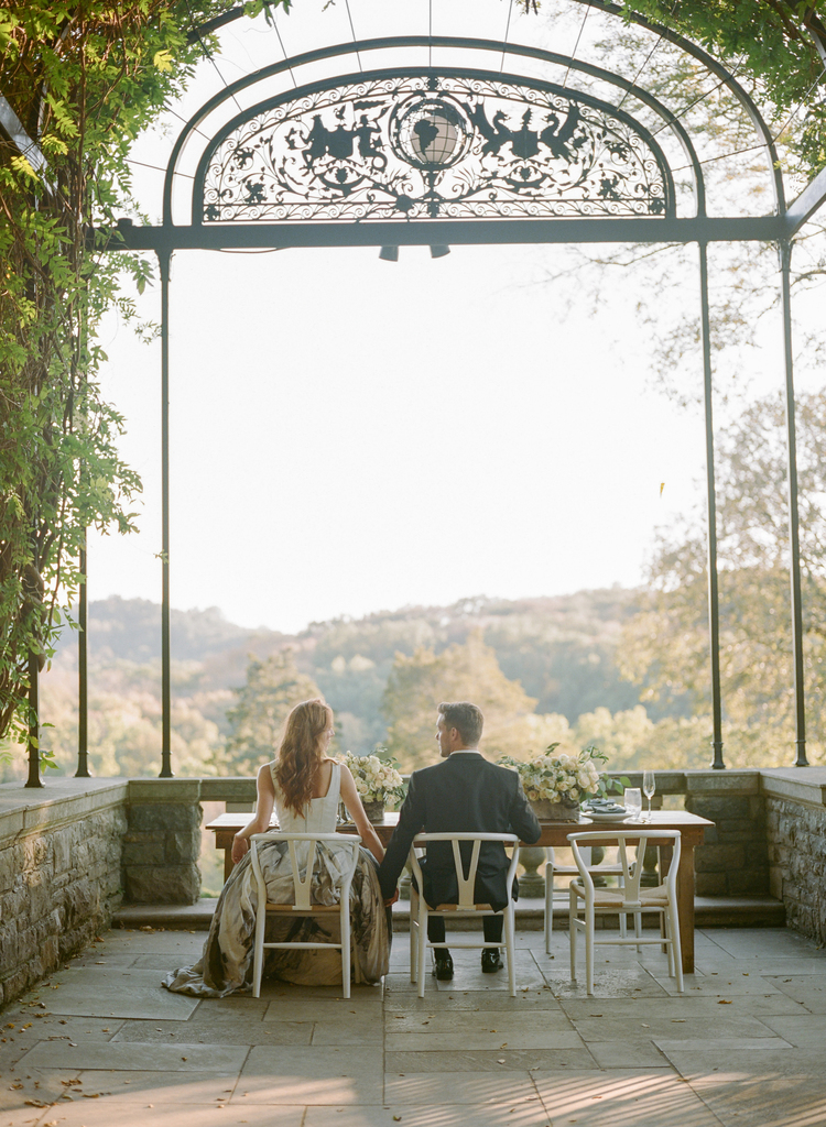 Couple sitting under a iron arch with ivy around it holding hands